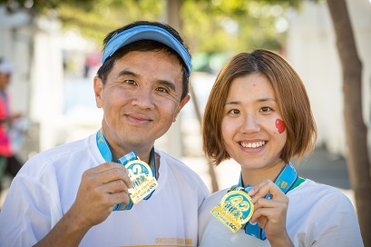 Two participants show off their marathon finisher medals