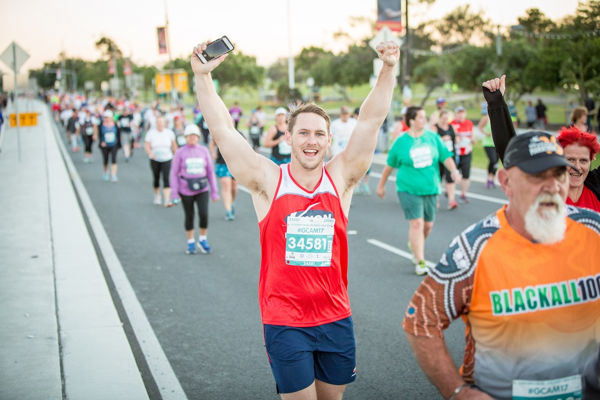 10km participant raises his arms in jubilation while running